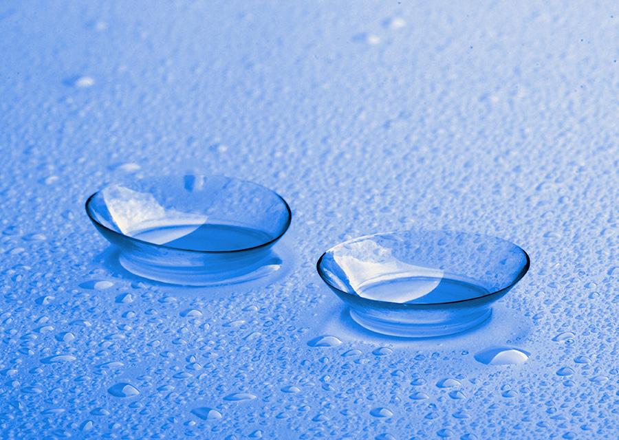 Dwie soczewki kontaktowe na mokrej, niebieskiej powierzchni