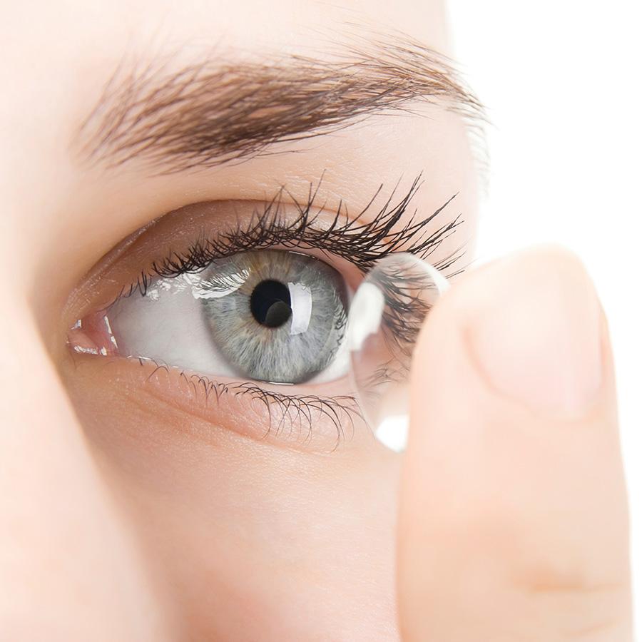 Kobieta podczas zakładania soczewki na oko