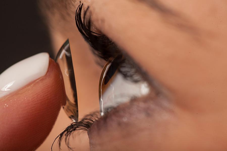 Zakładanie soczewki kontaktowej na oko kobiety